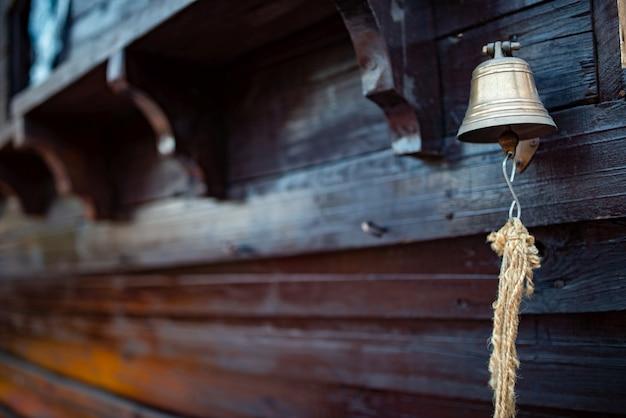 Колокол с веревкой висит на корпусе деревянного корабля. понятие уведомлений и аварийных ситуаций на корабле. место для рекламы