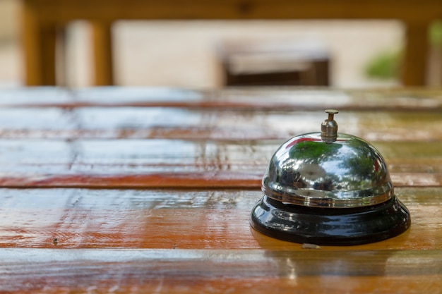 Bell on the wood table in restaurant with nature background