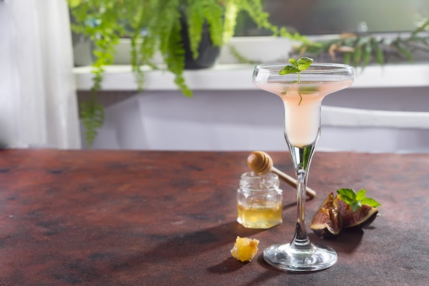 Bellini cocktail with peach and figs, honey on brown background over windows