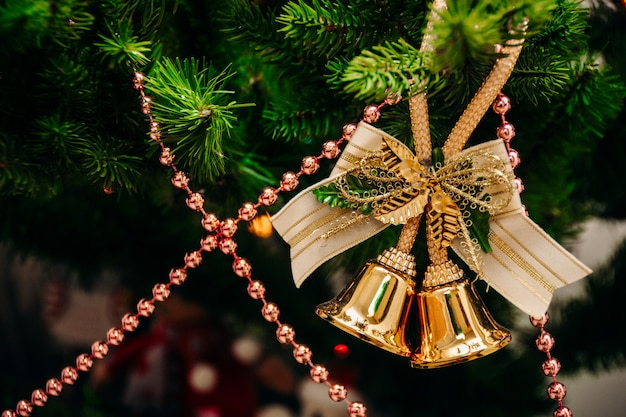 Bells hang on a branch of a christmas tree on a background of pink beads