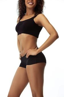 お腹とお尻。白い壁に隔離されたスリムな日焼けした女性の体。手入れの行き届いた形と肌を持つアフリカ系アメリカ人の女性モデル。美容、セルフケア、減量、フィットネス、痩身のコンセプト。