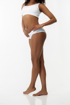 Belly and hips. slim tanned woman's back on white studio background. african-american model with well-kept shape and skin. beauty, self-care, weight loss, fitness, slimming concept. healthcare.