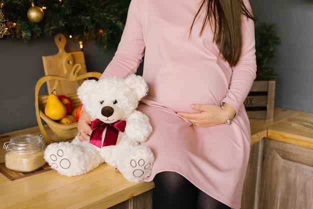 Живот беременной женщины в розовом трикотажном платье, она держит руку на животе, сидя рядом с мягкой игрушкой белого медведя с алым бантом