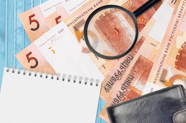 Купюры belorussian рублей и увеличительное стекло с черным кошельком