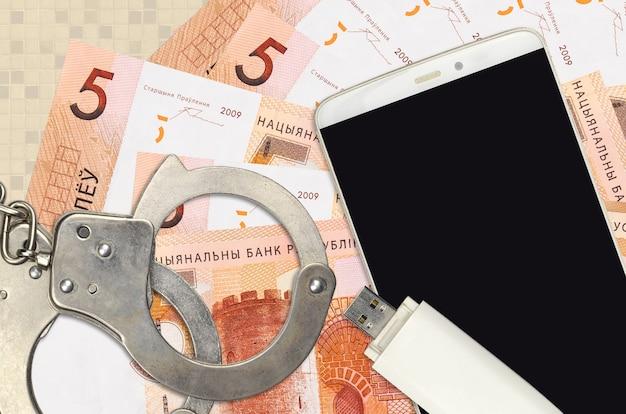 Белорусские купюры рублей и смартфон с полицейскими наручниками