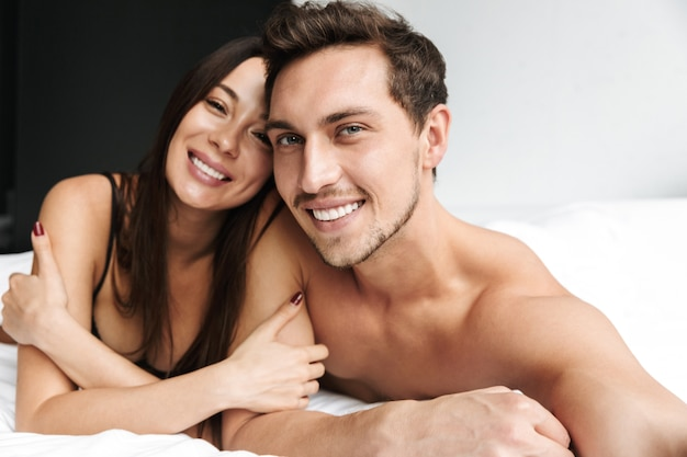 Beloved couple man and woman hugging together, while lying in bed at home or hotel apartment