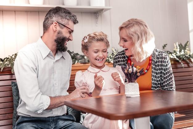 사랑하는 딸. 그들과 그녀의 시간을 즐기면서 그녀의 부모 사이에 앉아 귀여운 즐거운 소녀