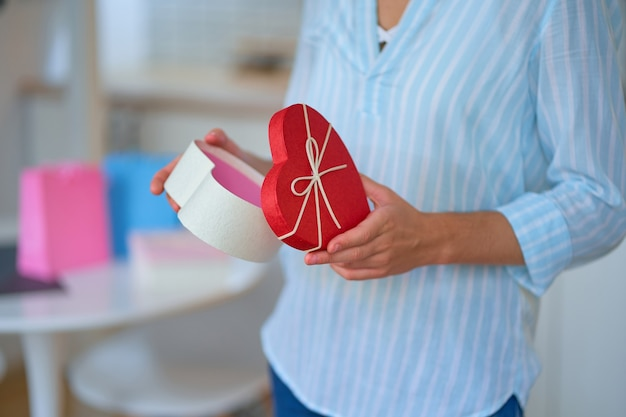 贈り物を受け取り、2月14日のバレンタインデーのためにハート型の箱を開ける最愛の女性