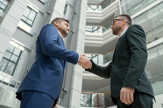 Ниже представлен вид мужчин-юристов в официальной одежде, стоящих в зале коммерческого центра и пожимающих друг другу руки как символ партнерства.