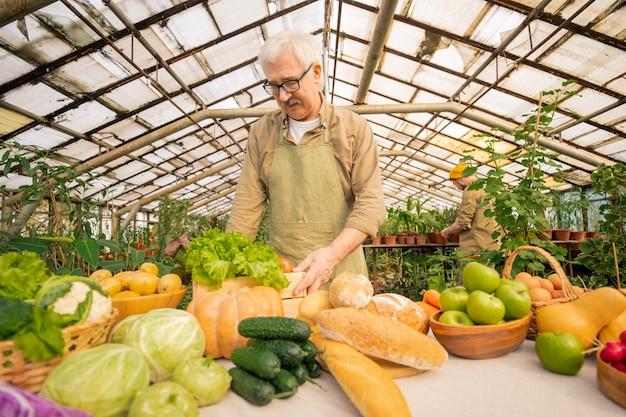 테이블에 서서 시장에서 판매하기 위해 자신의 유기농 제품을 준비하는 앞치마 수석 농부의보기 아래