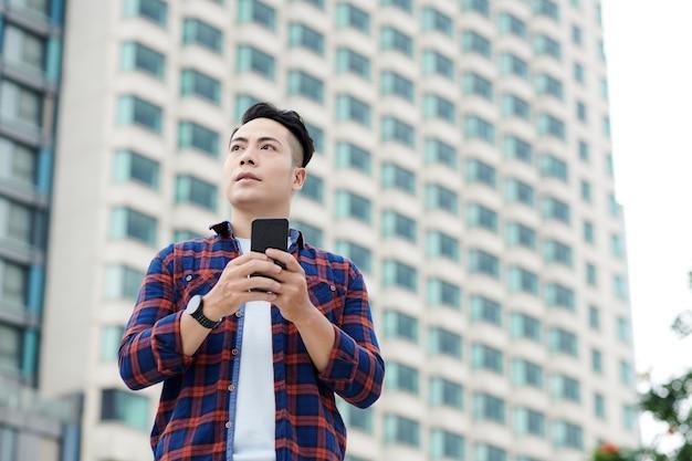 체크 무늬 셔츠를 입은 진지한 아시아 청년이 고층 빌딩에 기대어 서서 전화로 온라인 지도를 사용하는 모습 아래