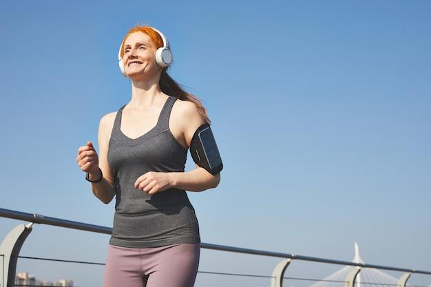 街を走っている間、ワイヤレスヘッドフォンで音楽を聴いている笑顔のエネルギッシュな赤毛の女性のビューの下