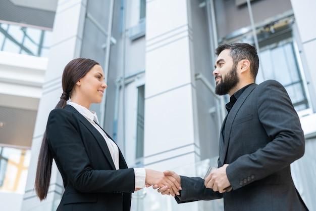オフィスで彼に挨拶しながら新しいビジネスパートナーと握手する笑顔の女性のビューの下