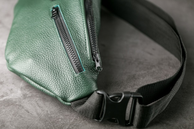 Belt bag made of dark green textured leather, banana on a gray table.