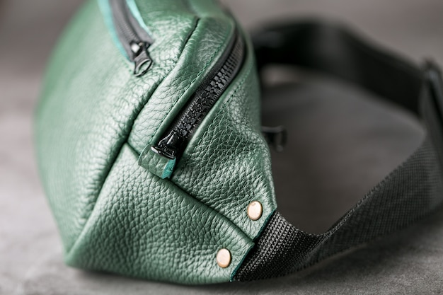 Belt bag made of dark green textured leather on gray
