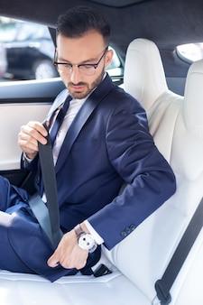 Ремень в машине. бородатый молодой бизнесмен в очках, пристегивая ремень безопасности в машине