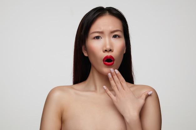 Ошеломленная молодая привлекательная брюнетка, подняв руку к лицу, удивленно глядя, округляя рот и нахмурив брови, позирует у белой стены