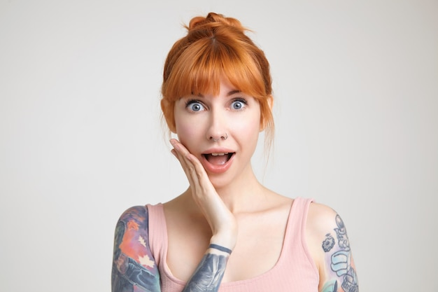 Bemused young attractive redhead tattooed female raising emotionally hand to her face while looking amazedly at camera, isolated over white background