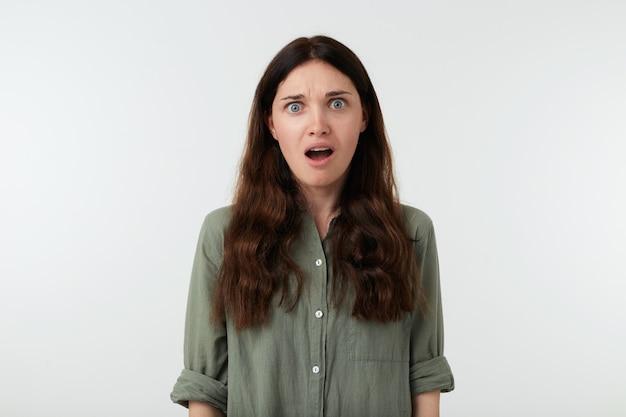 Perplessa giovane signora bruna dai capelli lunghi con acconciatura ondulata