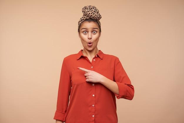 Perplessa giovane adorabile signora dai capelli castani con la fascia che arrotonda sorprendentemente i suoi occhi verdi mentre guarda con stupore davanti e indica da parte con l'indice, isolato su un muro beige