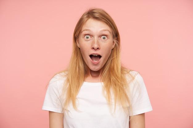 분홍색 배경 위에 절연 넓은 눈과 입으로 카메라를 놀라게보고 캐주얼 헤어 스타일을 가진 멍청한 젊은 사랑스러운 빨간 머리 여자가 열렸습니다.