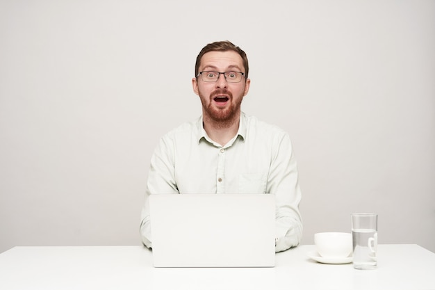 Bemused young pretty bearded man dressed in white shirt looking surprisedly at camera with wide mouth opened while typing text on his laptop, isolated over white background