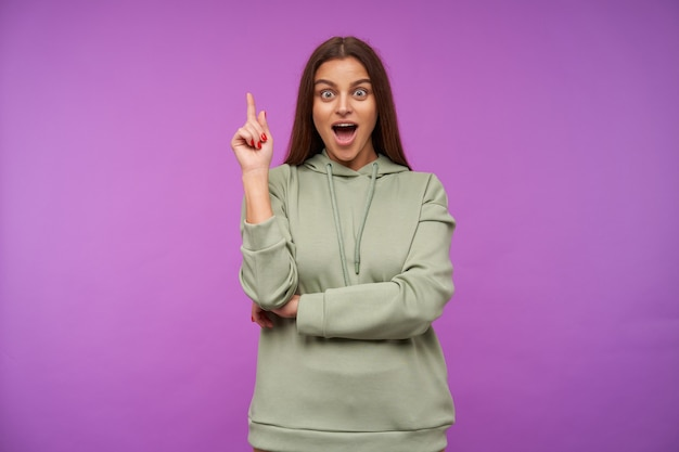 Bemused young pretty brunette woman with loose hair raising excitedly forefinger while looking at front with wide eyes and mouth opened, standing over purple wall