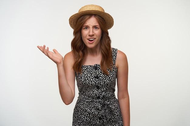 Perplessa giovane bella signora con i capelli rossi in posa, alzando la mano perplessa e contraendo la fronte, indossando abiti femminili e cappello di paglia