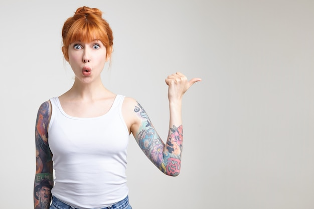 Perplesso giovane donna tatuata piuttosto rossa con acconciatura bun guardando stordito la fotocamera con gli occhi spalancati mentre mostra da parte, in posa su sfondo bianco