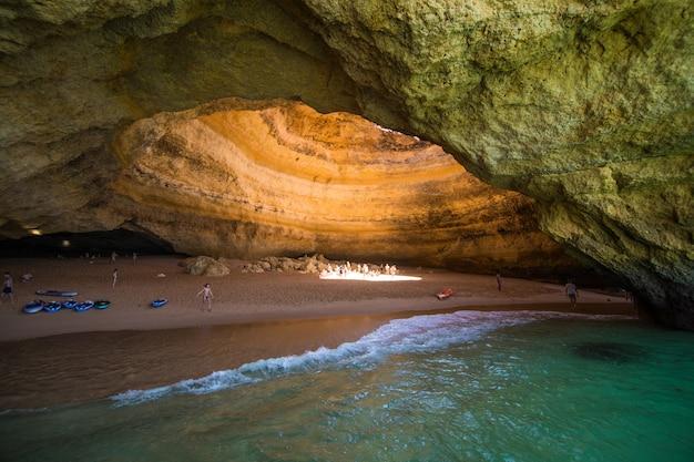 Прогулка на лодке по пещере бенагил в альгар-де-бенагил, пещере, включенной в 10 лучших пещер мира. побережье алгарве около лагоа, португалия. туристы посещают популярную достопримечательность