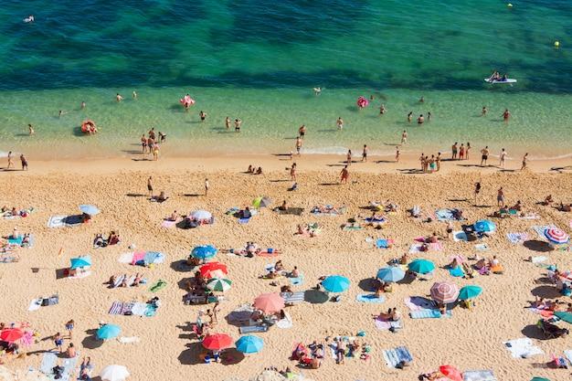 Летний отдых в португалии. толпа купающихся на пляже benagil в алгарве