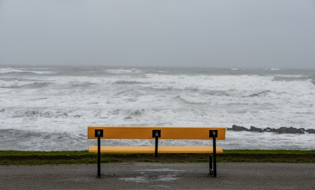 Bench on the beach surrounded by the sea under a cloudy sky during the storm
