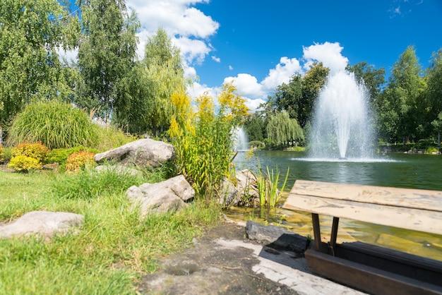 경치 좋은 풍경에 잎이 많은 푸른 나무로 둘러싸인 호수의 장식용 분수가 내려다 보이는 공원 벤치