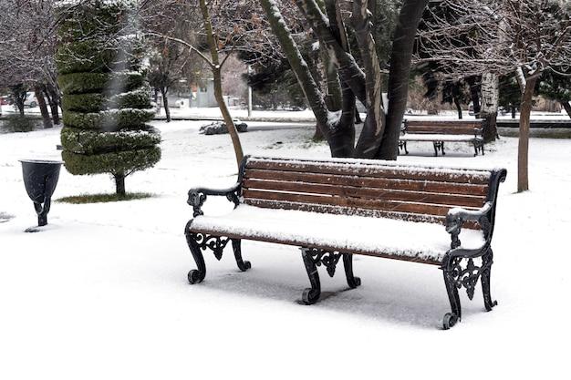 都市公園のベンチは雪で覆われています