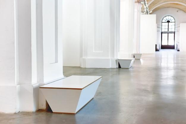 기둥이 있는 흰색 박물관 홀의 벤치