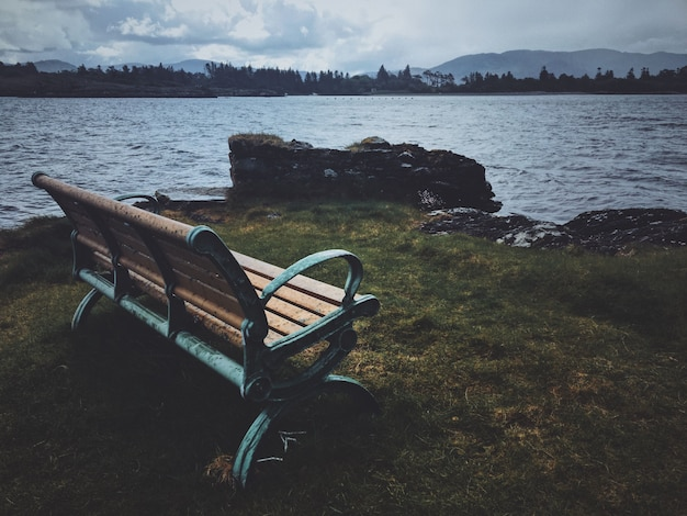 Bench near a cliff with a view of the sea and forest