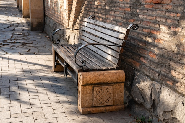 Bench in the park near the brick fence. recreation