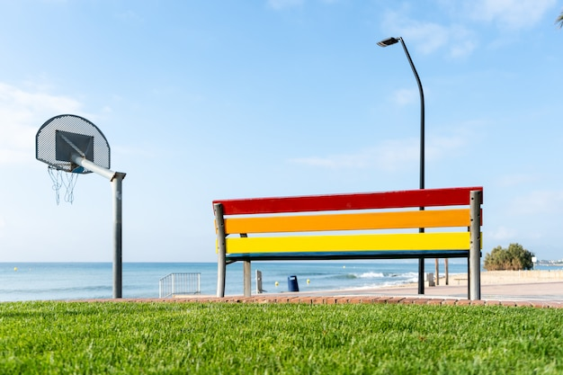 Bench in the park with the colors of the gay flag