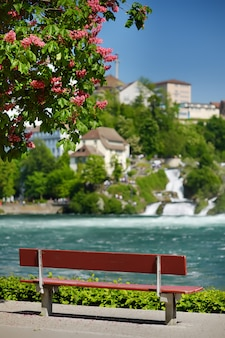 Bench on shore of rhine falls.