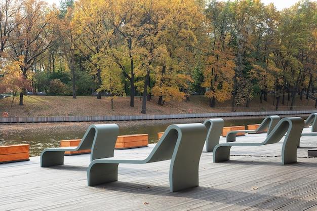 秋の都市公園でのレクリエーションのためのベンチとサンベッド