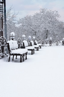 Benches and lanterns in the park covered with snow in winter in snowfall