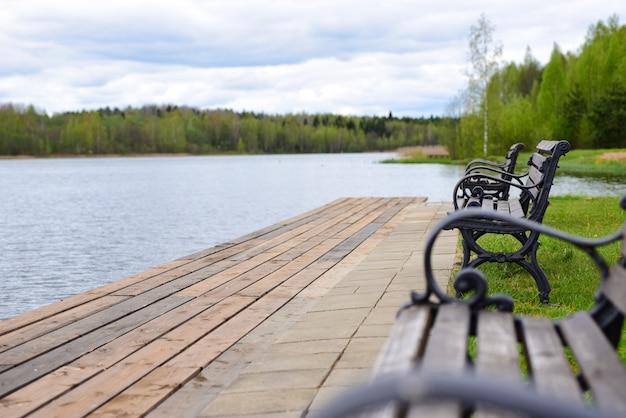 森の湖のほとりのベンチ