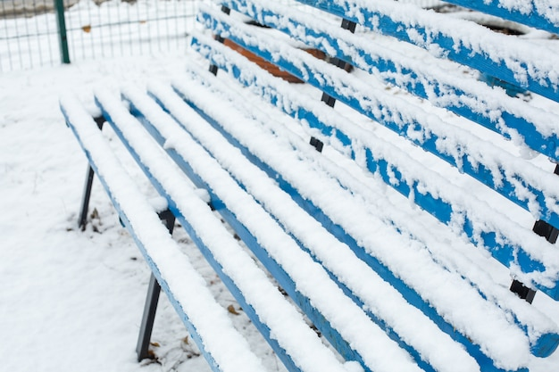 Benches for rest are covered with snow in the park in winter