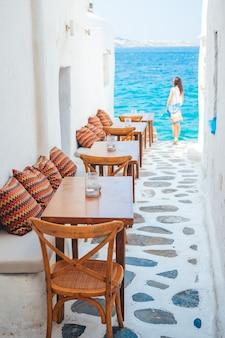 키 클라 데스 제도의 놀라운 바다 전망이있는 미코노스의 전형적인 그리스 야외 카페에서 베개가 달린 벤치