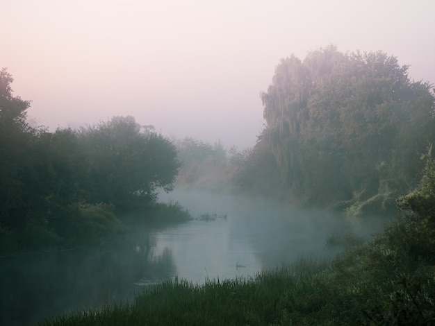 Bend of a small river in heavy fog at dawn