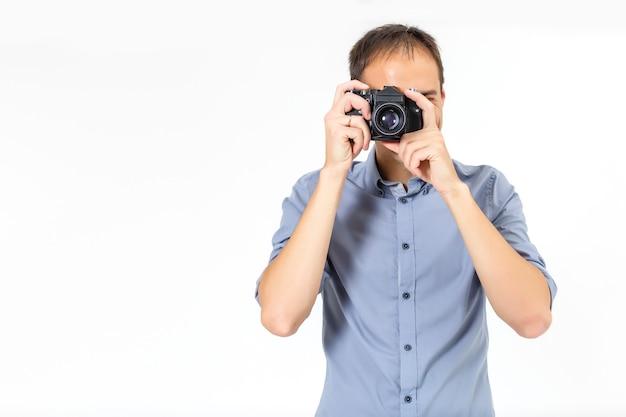 디지털 카메라 측면 보기와 함께 사진을 찍고 젊은 남자를 구부립니다. 흰색 배경 위에 절연입니다.