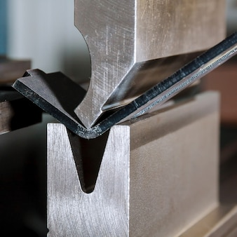Bending sheet metal on a hydraulic machine at the factory. bend tools, press brake punch and die. close-up.