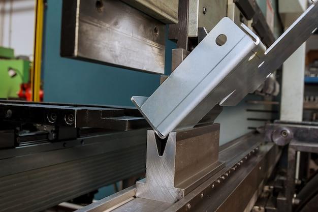 Гибка листового металла на гидравлическом станке в заводских условиях. согните инструменты, нажмите тормозной пуансон и умрите. крупный план.