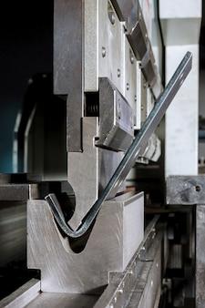 공장에서 유압 기계로 판금을 굽힘. 벤드 도구, 프레스 브레이크 펀치 및 다이. 확대.
