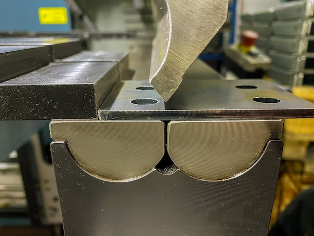 Bending of sheet metal parts using a sheet metal bending machine in factory
